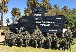 Camouflage uniformed and armored police officers posing beside a SWAT vehicle.