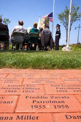 People seated with close up angled view of bricks with words on them.